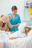 Nurse holding a teddy bear — Stock Photo