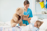 Nurse showing a teddy bear to a child — Stock Photo