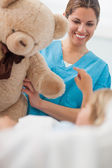 Happy nurse holding a teddy bear — Stock Photo
