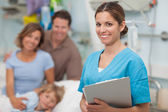 Enfermera sosteniendo un portapapeles junto a una familia — Foto de Stock