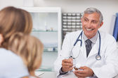 Smiling doctor writing on a drug box — Stock Photo