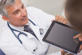 Doctor holding a tablet computer while looking at a patient — Stock Photo