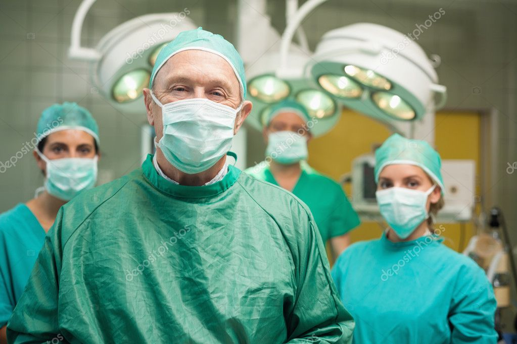 Smiling surgeon posing with a team in a surgical room — Stock Photo #14146908