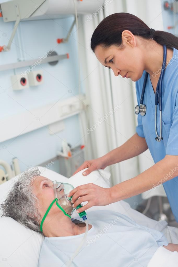 Nurse putting oxygen mask on a patient in hospital ward — Stock Photo #14148386