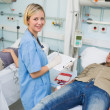 Stock Photo: Nurse looking at camernext to transfused patients