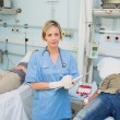 Stock Photo: Nurse holding a clipboard next to transfused patients