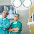 Serious surgeon and a nurse looking at camera — Stock Photo