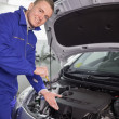 Smiling mechanic showing an engine — Stockfoto #14152490