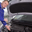 Stock Photo: Mechanic showing engine with his hand