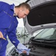 Mechanic looking at the dipstick — Stock Photo