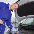 Stock Photo: Mechanic holding dipstick