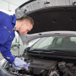 Mechanic looking at a dipstick while holding it - Stock Photo