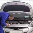 Stock Photo: Mechanic leaning on car