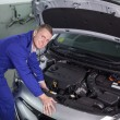 Stock Photo: Mechanic repairing engine of car