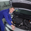 Stock Photo: Mechanic repairing a car engine