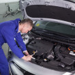 Stock Photo: Concentrated mechanic repairing car