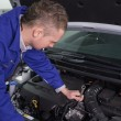 Stock Photo: Mechanic repairing engine with spanner