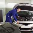 Stock Photo: Smiling mechanic leaning on car next to computer