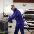 Smiling mechanic using a computer — Stock Photo
