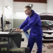 Stock Photo: Concentrated mechanic using computer
