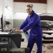 Mechanic using a computer while smiling — Stock Photo