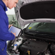 Mechanic testing the engine with a tablet computer - Foto Stock