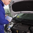 Mechanic testing the engine with a tablet computer - Foto de Stock  