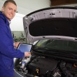 Mechanic looking at camerwhile holding tablet computer — Stock Photo #14152659