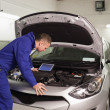 Concentrated mechanic looking at a car engine — Stock Photo