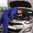 Mechanic looking at a car engine — Stock Photo
