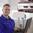 Smiling mechanic typing on a laptop — Stock Photo