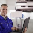Foto Stock: Smiling mechanic using a laptop