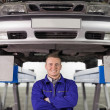 Stock Photo: Mechanic with arms crossed below car