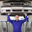 Smiling mechanic touching below of car — Stock Photo #14152843