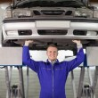 Stock Photo: Smiling mechanic touching below of car