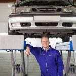 Smiling mechanic below a car — Stock Photo