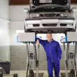 Smiling mechanic leaning on a machine below a car — Foto de Stock