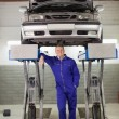 Smiling mechanic standing below car — Stock Photo #14152852