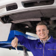 Stock Photo: Mechanic holding spanner below car