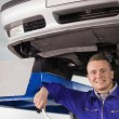 Smiling mechanic holding spanner below car — Stock Photo #14152858