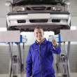 Smiling mechanic standing with thumb up — Stock Photo
