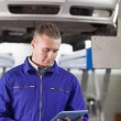 Mechanic looking at a tablet computer while holding it — Stock Photo