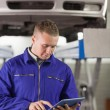 Concentrated mechanic holding a tablet computer — Stock Photo #14152905