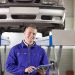 Stock Photo: Mechanic touching tablet computer while looking at camera