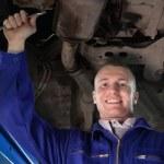 Smiling mechanic looking at camera below a car — Stock Photo #14152955