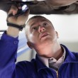 Stock Photo: Mechanic illuminating below of car with flashlight