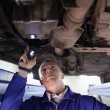 Stock Photo: Concentrated mechanic illuminating car with flashlight