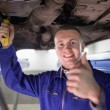 Smiling man repairing a car with his thumb up — Stock Photo