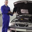 Foto de Stock  : Mechanic standing while holding a computer