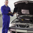 Mechanic standing while holding a computer - Stock Photo